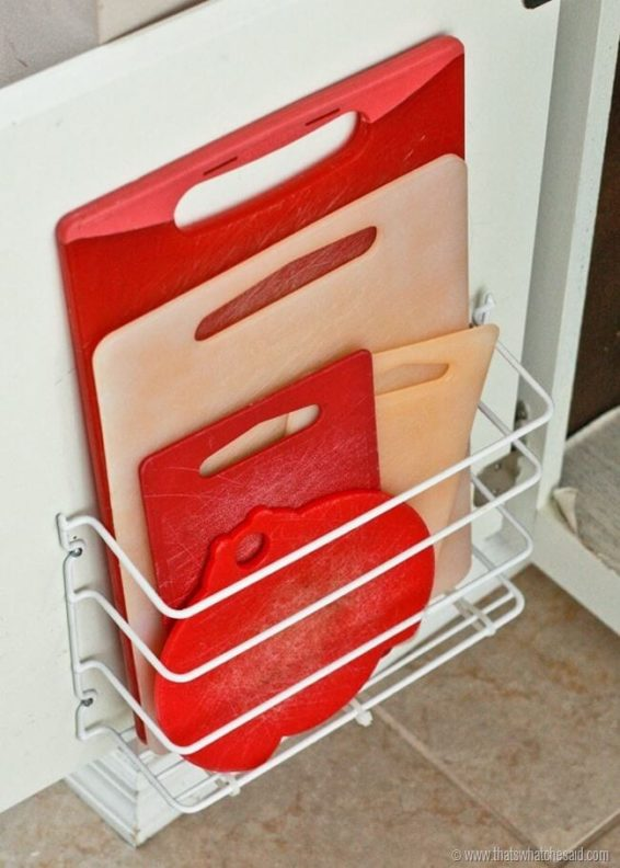 Cutting boards stored inside a wire organizer attached to cabinet door