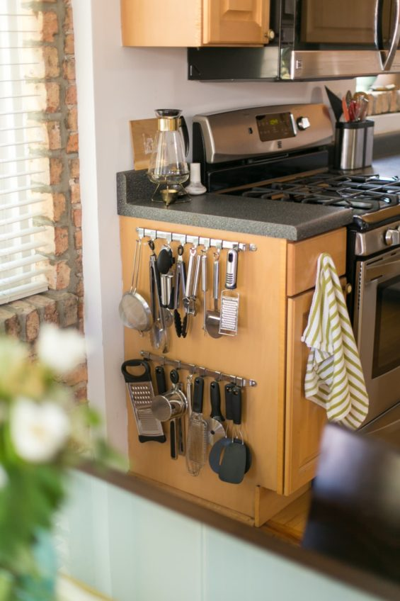Kitchen tools hanging on the side of a kitchen cabinet