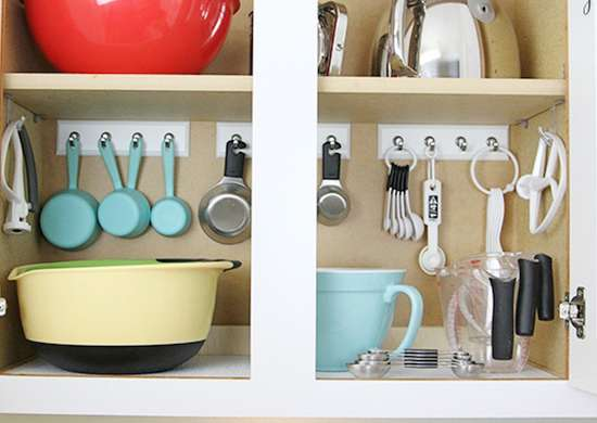 The inside of a kitchen cabinet with measurement spoons hanging on key rails
