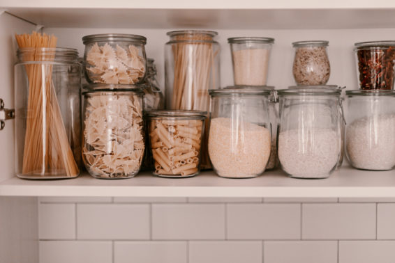 Ingredients stored in glass containers inside a kitchen cabinet