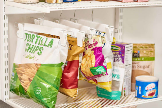 Snack bags hanging from pant hangers on wire shelves