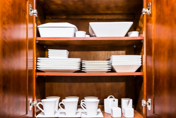 Organized dishes and cups in a kitchen cabinet