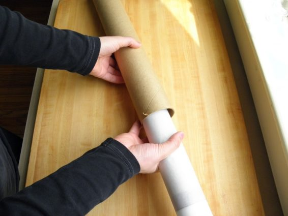 Slipping silicon mat rolled in parchment paper into a mailing tube